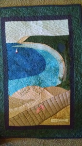 Once assembled I did some free-motion embroidery for the tree, grass, flip-flop detail and wood grain on the ends of the walkway planks.  When this was finished I made my quilt sandwich and proceeded to the fun part of free-motion quilting.